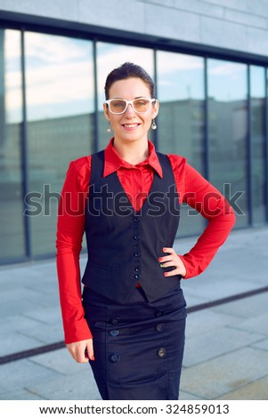 Stylish modern woman with glasses. She is a business coach or teacher. Business woman in a red blouse, black suit, skirt. Woman stands on the background of the business center. Occupation architect. - stock photo
