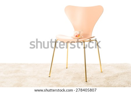 Stylish moulded modern chair with metal legs and a porcelain teacup standing on the vacant seat in a room interior with a white wall and copyspace - stock photo
