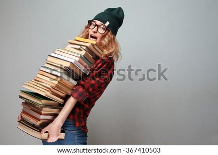 stylish nerd girl with many books - stock photo
