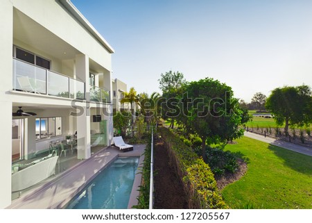 Stylish new house with covered patio and swimming pool - stock photo