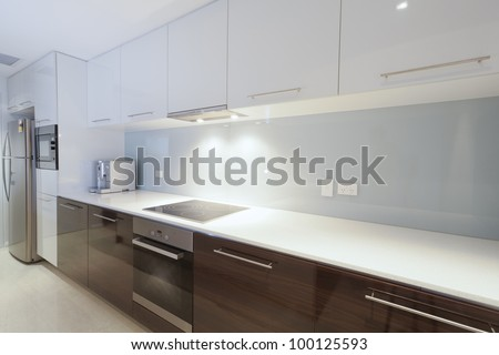 Stylish new kitchen with stainless steel oven, stove, coffee machine and fridge. - stock photo