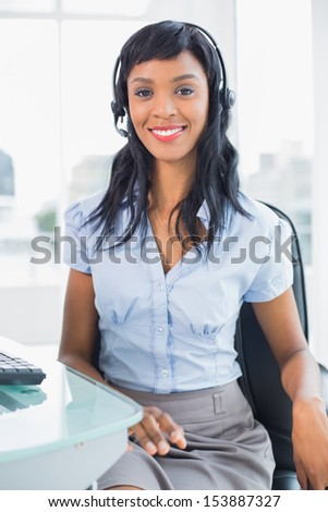Stylish operator smiling and looking at camera in office - stock photo