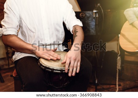 stylish percussionist playing on leather drum on a concert, hands motion - stock photo