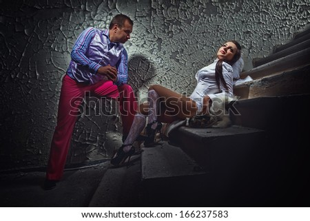 Stylish pimp and his bride women dark basement - stock photo