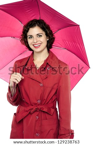 Stylish portrait of a smiling young female model holding an umbrella. - stock photo