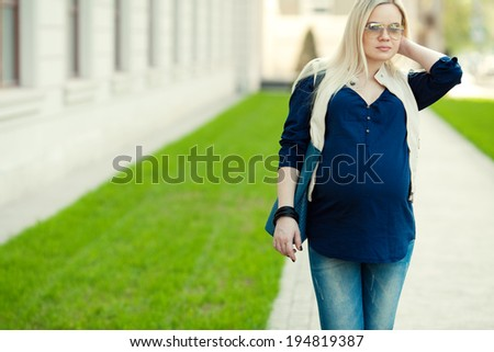 Stylish Pregnancy Concept. Portrait of a fashionable mommy with long blond hair wearing casual trendy clothes and sunglasses and going shopping with blue leather bag. Sunny weather. Outdoor shot - stock photo