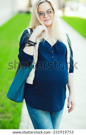 Stylish Pregnancy Concept. Portrait of fashionable mommy with long blond hair wearing casual trendy clothes, eyewear and going shopping with blue leather bag. Sunny weather. Outdoor shot - stock photo