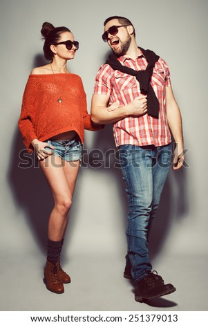 Stylish pregnancy & family concept: portrait of funny couple of hipsters (husband and wife) in trendy casual clothing, eyewear smiling and posing over gray background. Urban street style. Studio shot - stock photo