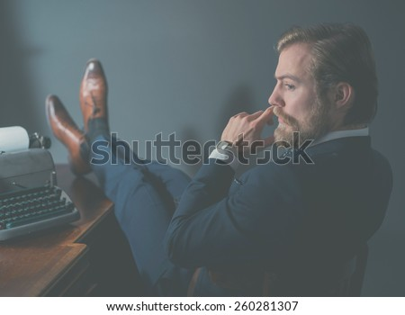 Stylish retro businessman in vintage fashion relaxing at his desk in the office with his feet up alongside an old manual typewriter - stock photo