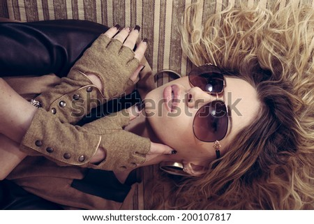 Stylish sexy hot glamor young woman with glasses gloves having fun relaxing lying on the couch crossed arms portrait image - stock photo