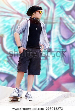 Stylish skater boy listening music standing outdoors on beautiful graffiti wall background, active teen life, hipster style, fashion lifestyle - stock photo