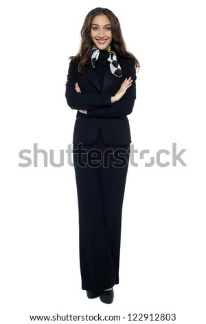 Stylish stewardess striking a confident pose with folded arms against white background. - stock photo