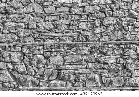 Stylish stone wall background in black and white - stock photo