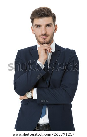 Stylish successful handsome young businessman standing in a relaxed pose with his hands in his pockets and his suit jacket open, isolated on white - stock photo