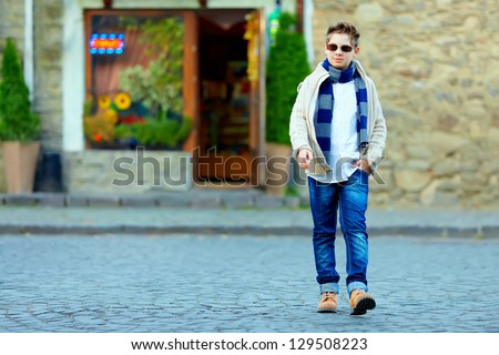 stylish teenage boy crossing the street of old town - stock photo