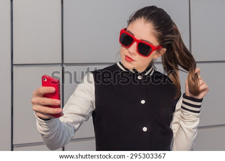 Stylish teenage girl in red sunglasses taking self portrait with mobile phone - stock photo