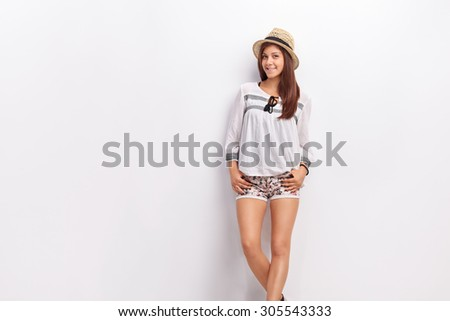 Stylish teenage girl leaning against a wall and looking at the camera - stock photo