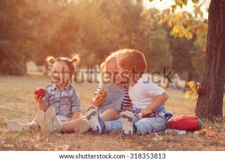 stylish toddlers. boy kissing girl - stock photo