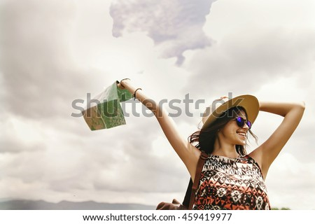 stylish traveler hipster woman with sunglasses and hat holding  map on top of mountains and sky, emotional happy moment, travel concept, space for text - stock photo