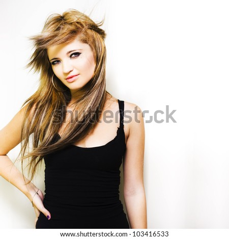 Stylish trendy and hip young blonde woman modelling a fresh new hair style in a hairdressing and hairstyle conceptual with space for text - stock photo
