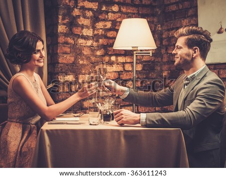 Stylish wealthy couple toasting with champagne in a restaurant. - stock photo
