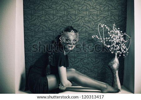 stylish woman in fetish clothes at wall hole - stock photo