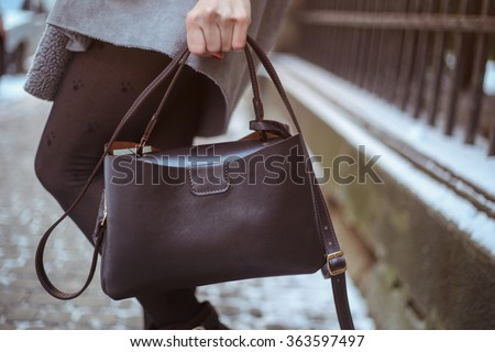 Stylish woman in gray trendy warm coat with dark brown leather bag walking down the snowy street - stock photo