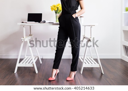 Stylish Woman standing in front of her desk. Depth of field, selective focus  - stock photo