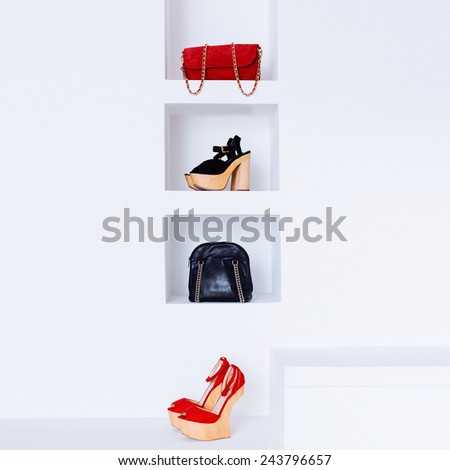 Stylish women's clothing in white interior. Shoes and Bags. Luxury accessories. Red and black combination in clothing. - stock photo