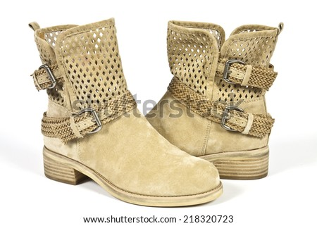 Stylish womens boots beige leather with metal buckles - stock photo