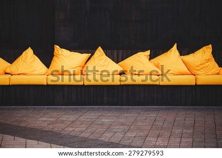 Stylish yellow sofa with cushions on a dark wall background - stock photo