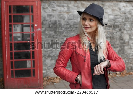 Stylish young blond woman in a red leather jacket and hat standing waiting outside a red telephone kiosk checking her watch and looking down the street - stock photo