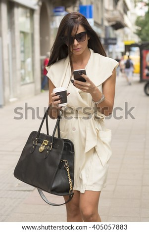 Stylish young business woman wearing short white dress and sunglasses texts in urban setting while holding coffee and bag - stock photo