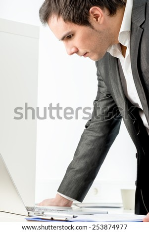 Stylish young businessman standing leaning on his desk reading a laptop computer with a serious expression, side view. - stock photo