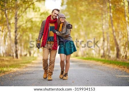 Stylish young couple enjoying walk in park - stock photo