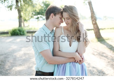 Stylish young couple in love embracing in the summer park - stock photo