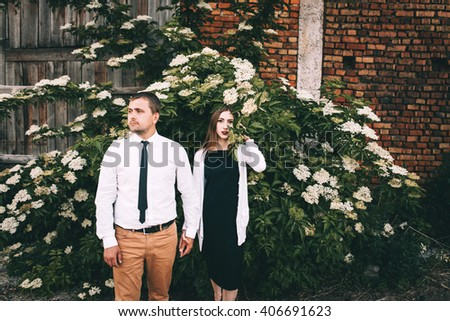 Stylish young couple posing beside an old brick building and a blooming white bush large... - stock photo