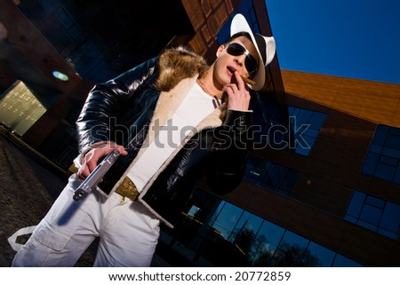 Stylish young gangster standing with a gun and cigar outdoors - stock photo
