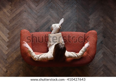 Stylish young girl in beige suit reads a book on the red sofa. Top view - stock photo