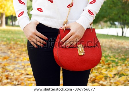 Stylish young girl with red handbag . Autumn outfit pullover black jeans - stock photo
