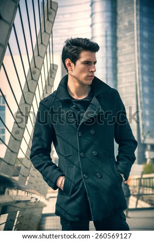 Stylish Young Handsome Man in Black Coat Standing in City Center Street with Skyscraper Behind Him, Looking to the Right of the Frame. - stock photo