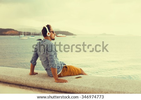 stylish young man in a shirt and shorts and sneakers listening to music in headphones on a smartphone and is sitting on pier looking at sea on yachts boats and the sunset,music lounge ,relaxing  - stock photo