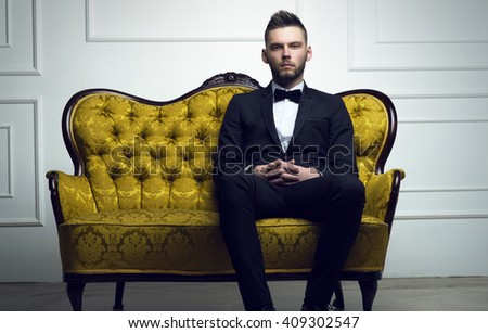 Stylish young man in a suit and bow tie. Business style. Fashionable image. Evening dress. Sexy man standing and looking at the camera. Fashion look - stock photo