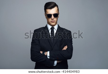 Stylish young man in suit and sunglasses. Business style. Fashionable image. Office worker. Sexy man standing and looking at the camera - stock photo