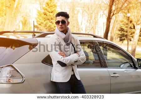 Stylish young man is leaning on a beautiful new SUV in the sunset - stock photo