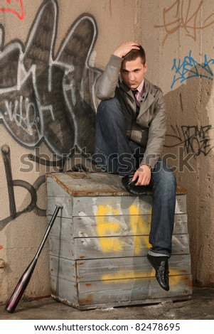 stylish young man posing on wooden sandbox - stock photo
