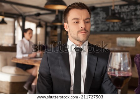 Stylish young man sitting in bar. Handsome man drinking glass of red wine in bar  - stock photo