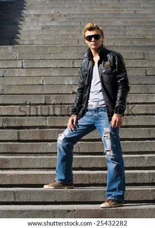 Stylish young man stands on the stair - stock photo
