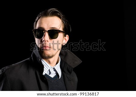 stylish young man wearing sunglasses looking away. - stock photo