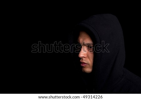 Stylish young man with hoodie over a black background. - stock photo